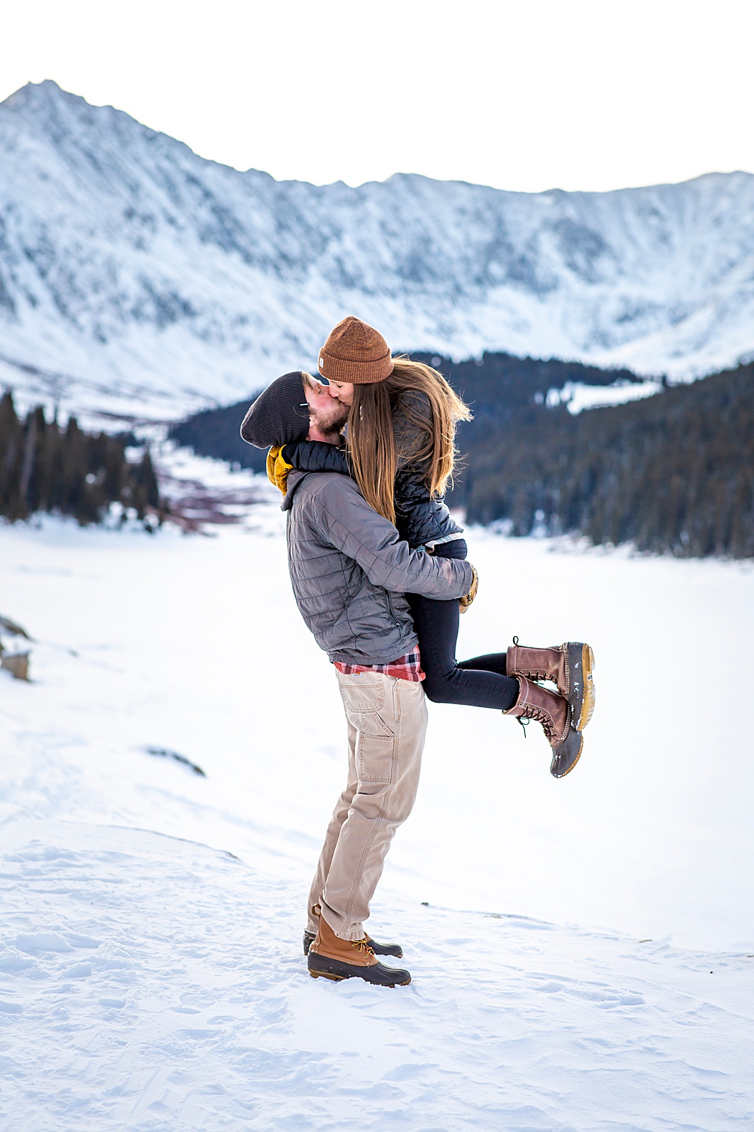 Man lifts woman for a kiss in Breckenridge, Colorado. Engagement Photo taken by Hillary Shedd Photography, Colorado Wedding Photographer.