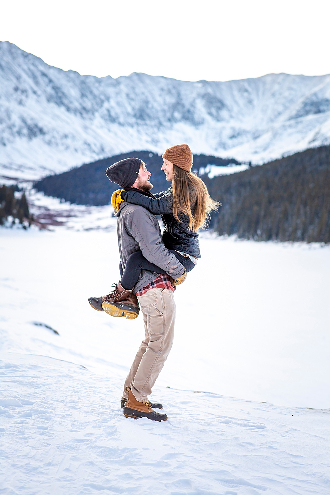 Woman wraps legs around her fiance in Breckenridge, Colorado. Engagement photo taken by Hillary Shedd Photography, Colorado Wedding Photographer