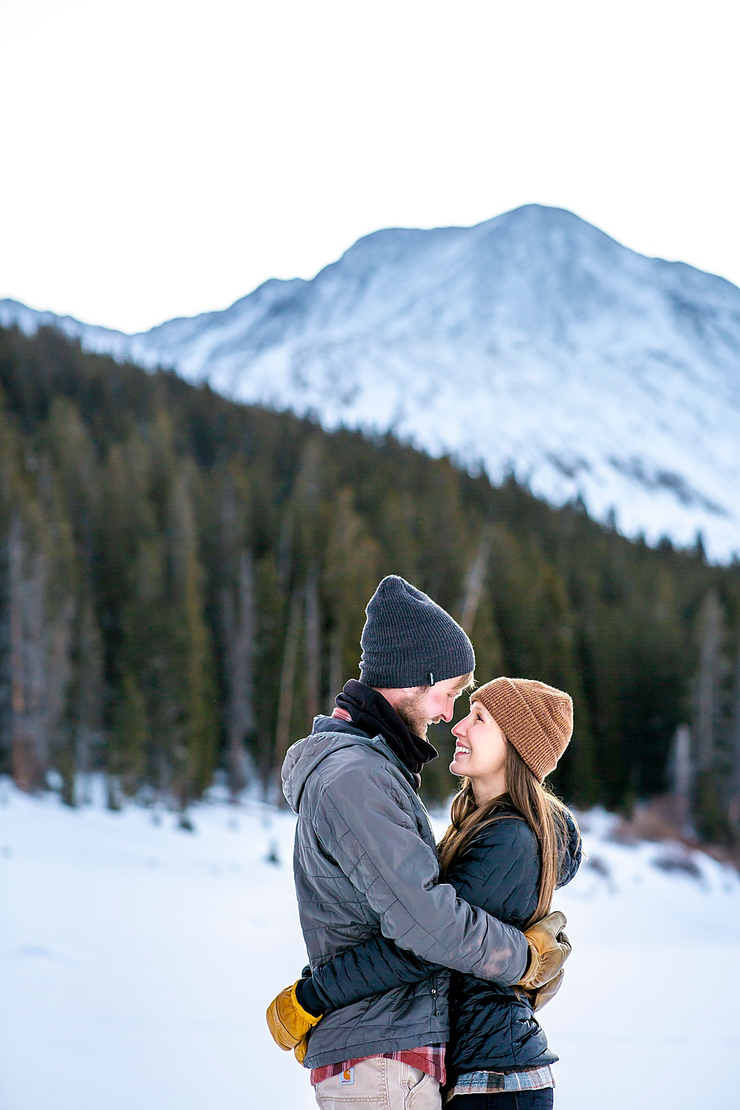 Couple hugs with snowy mountain in the background during a winter engagement shoot in Breckenridge, Colorado taken by Hillary Shedd Photography, Colorado Wedding Photographer.