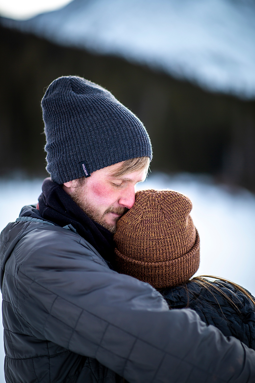 Cute couple photo of man hugging woman in the snow during their winter engagement session in Breckenridge, Colorado taken by Hillary Shedd Photography, Colorado Wedding Photographer.