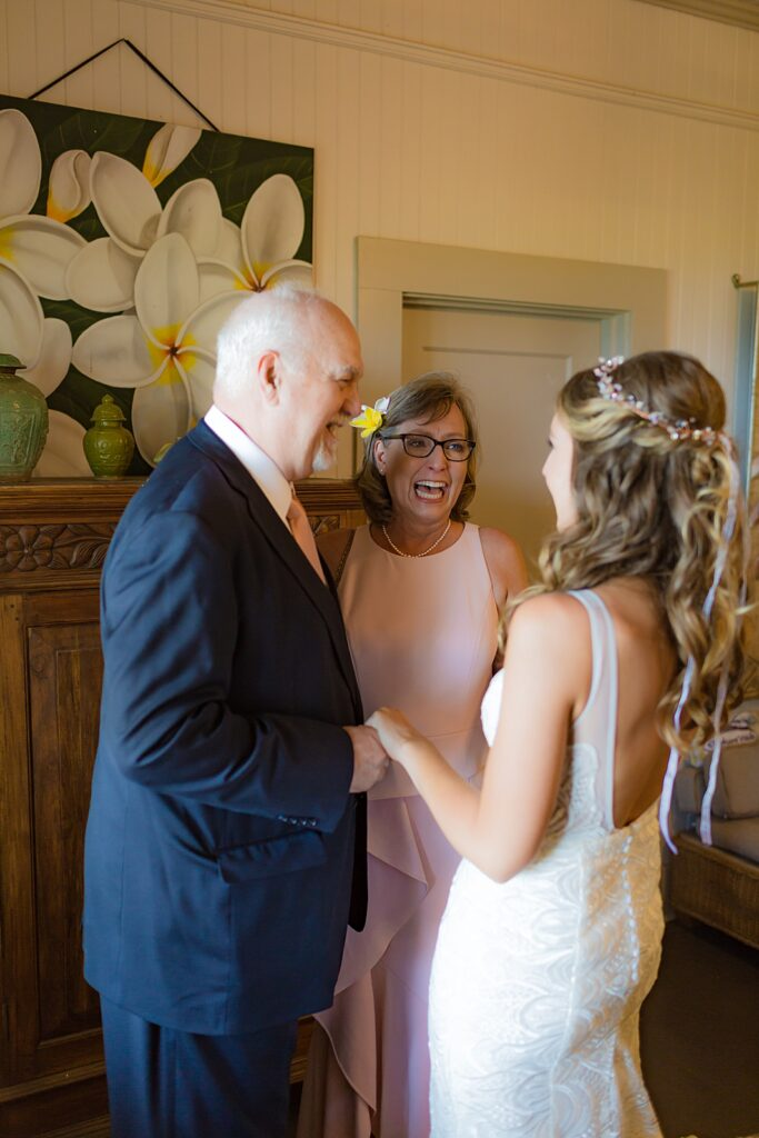 bride laughing with mom and dad before wedding