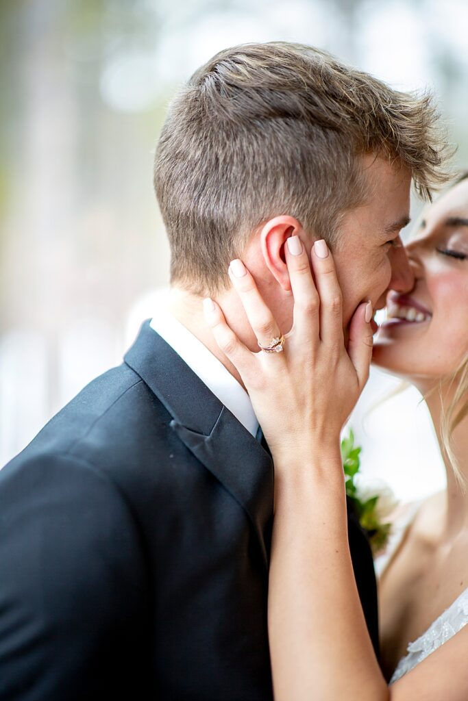 Bride kissing groom and showing ring