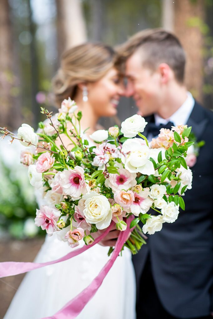 Pink and white bouquet with wedding bride and groom in the background.